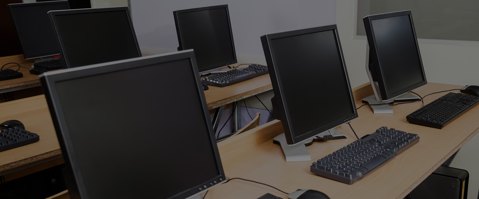 Row of computers on desks in classroom